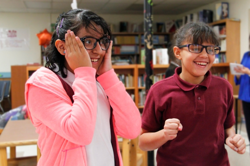 Children smiling while trying on new eyeglasses