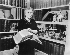 Helen Keller stands in a library holding an open book and smiling