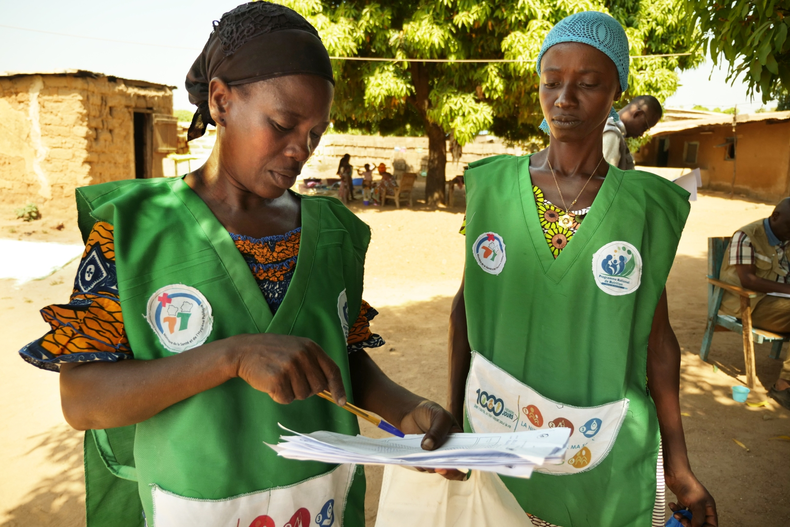 Two community health workers reviewing paperwork