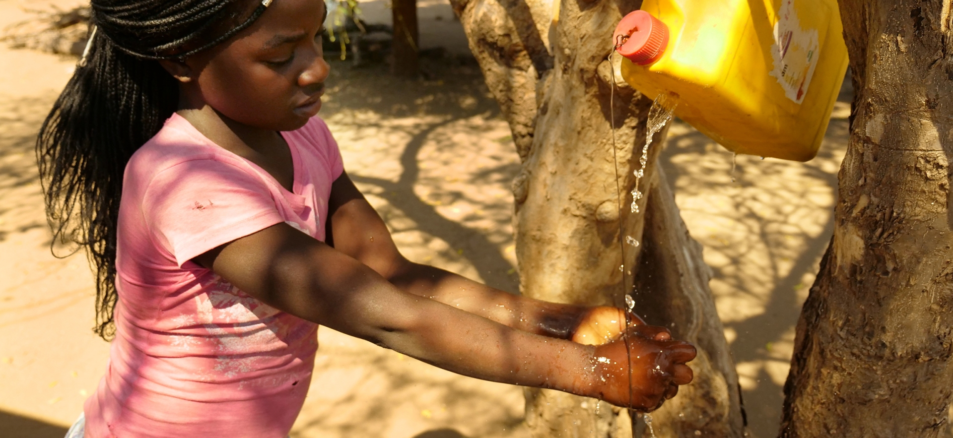 A young girl uses a hands-free device to pour water for washing her hands.