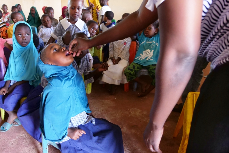 A girl at Funzi Island Primary School receives a dose of vitamin A supplementation as her classmates look on