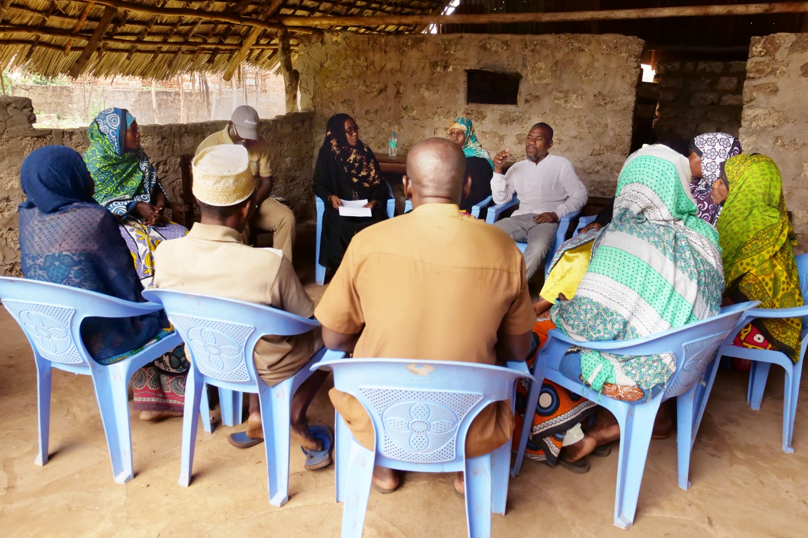 Community members sit in a circle of plastic chairs, participating in a community dialogue led by Sharmilla