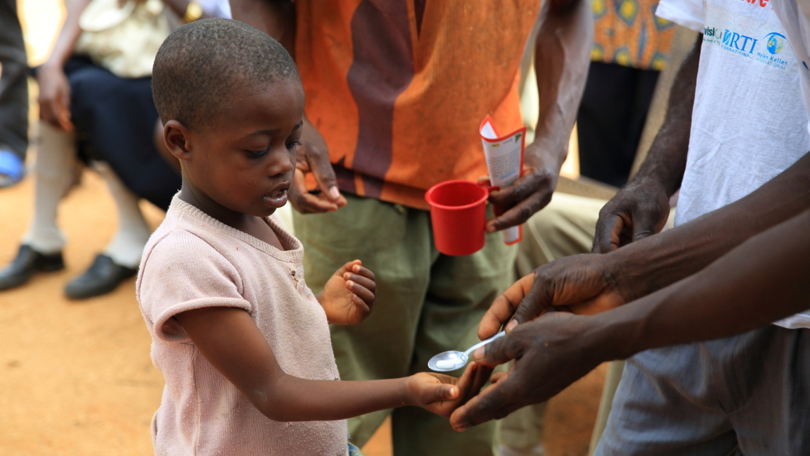 A young child receives a dose of medicine