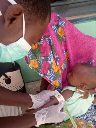 A community health worker measures an infant's mid-upper arm circumference