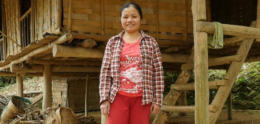 Ha Thi Theu stands in front of her home
