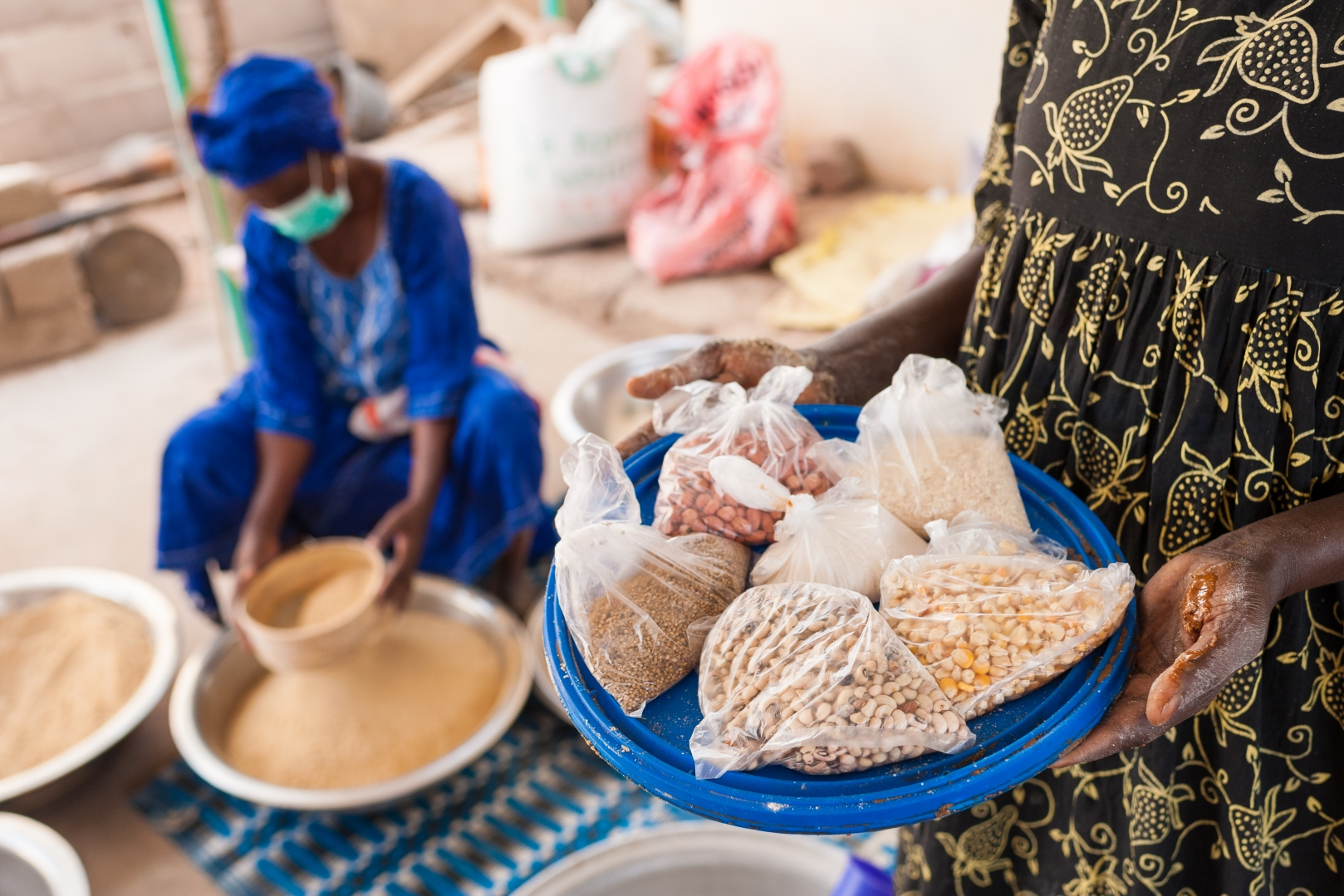 In the foreground, a woman holds a tray the ingredients used to make a nutrient-rich flour blend that is being sifted by the women in the background