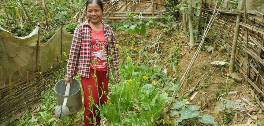 Theu waters the vegetables she is growing on her land