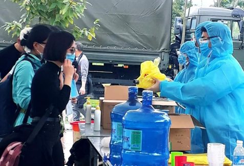 The Hoa Binh Center for Disease Control gives out soap and hand sanitizer to residents inside a quarantine area at a military base in Hoa Binh province