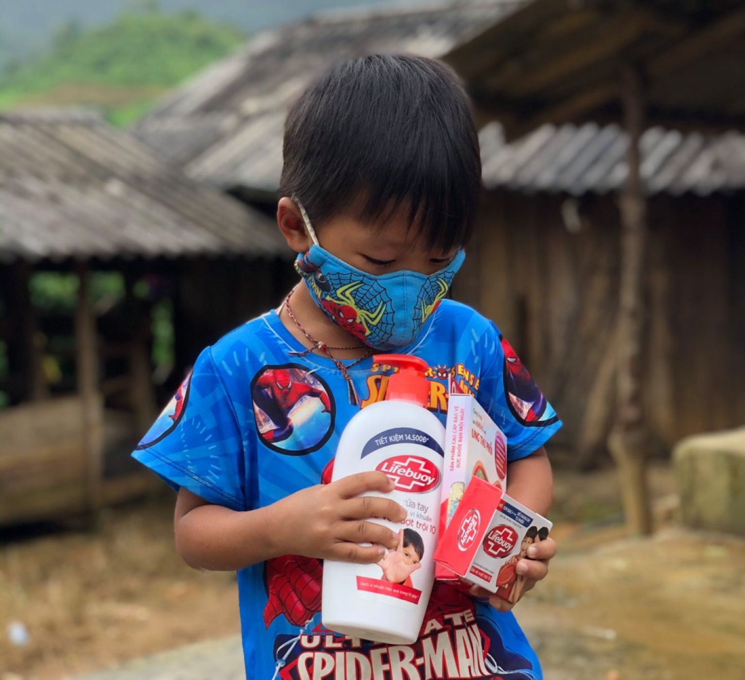 A boy holds hand sanitizer and masks that he received in his COVID prevention kit from Helen Keller.