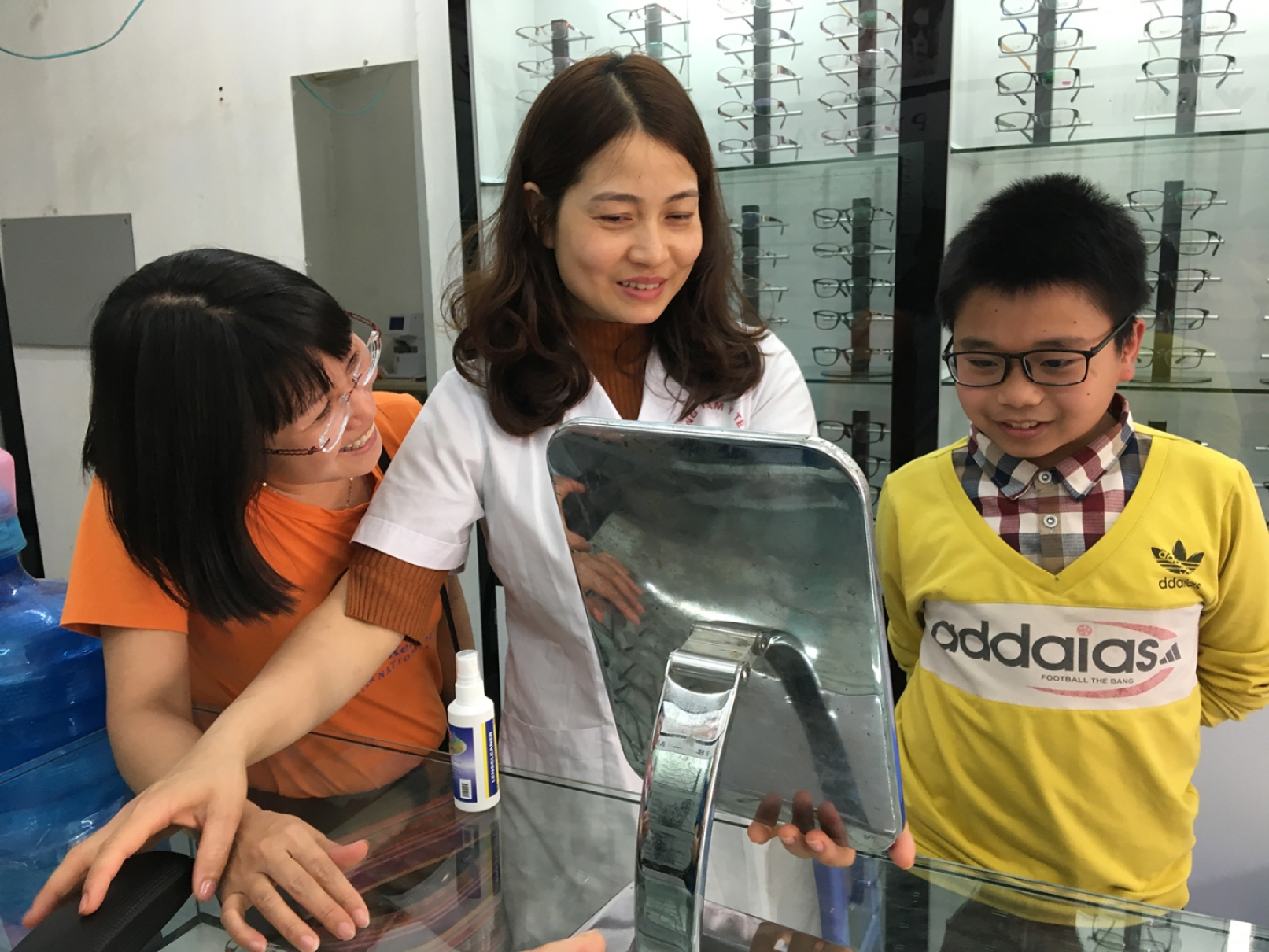 Ngoc looks on as an optician helps a boy choose eye glasses that will not only help him see, but that he will also be proud to wear