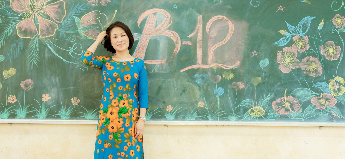 Pham Kim Ngoc stands in front of a chalkboard