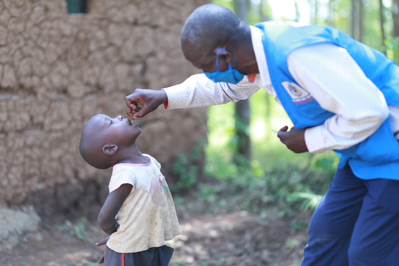 A health volunteer squeezes vitamin A drops into a young boy's mouth while wearing a mask.