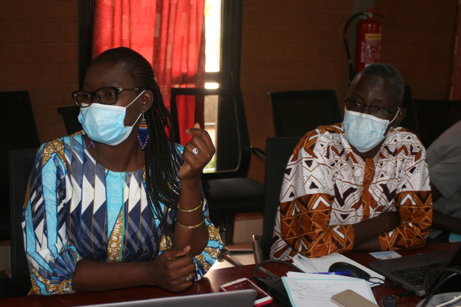 A nurse and colleague sitting at a table and wearing face masks