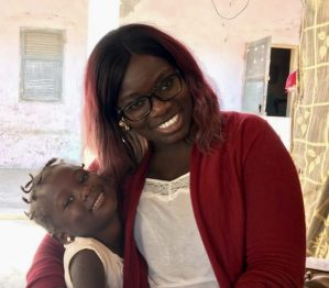 Maguette Beye with a young girl who lives in a community served by a health clinic that Helen Keller supports
