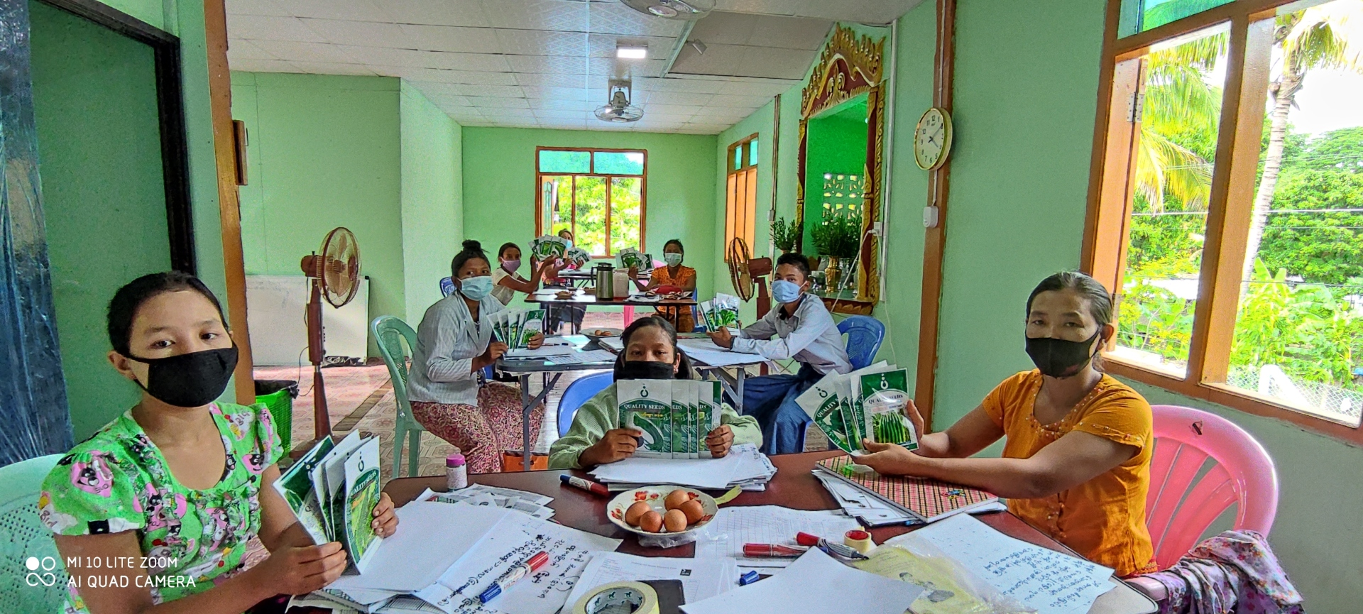 Community health volunteers sit around a table holding seed packages