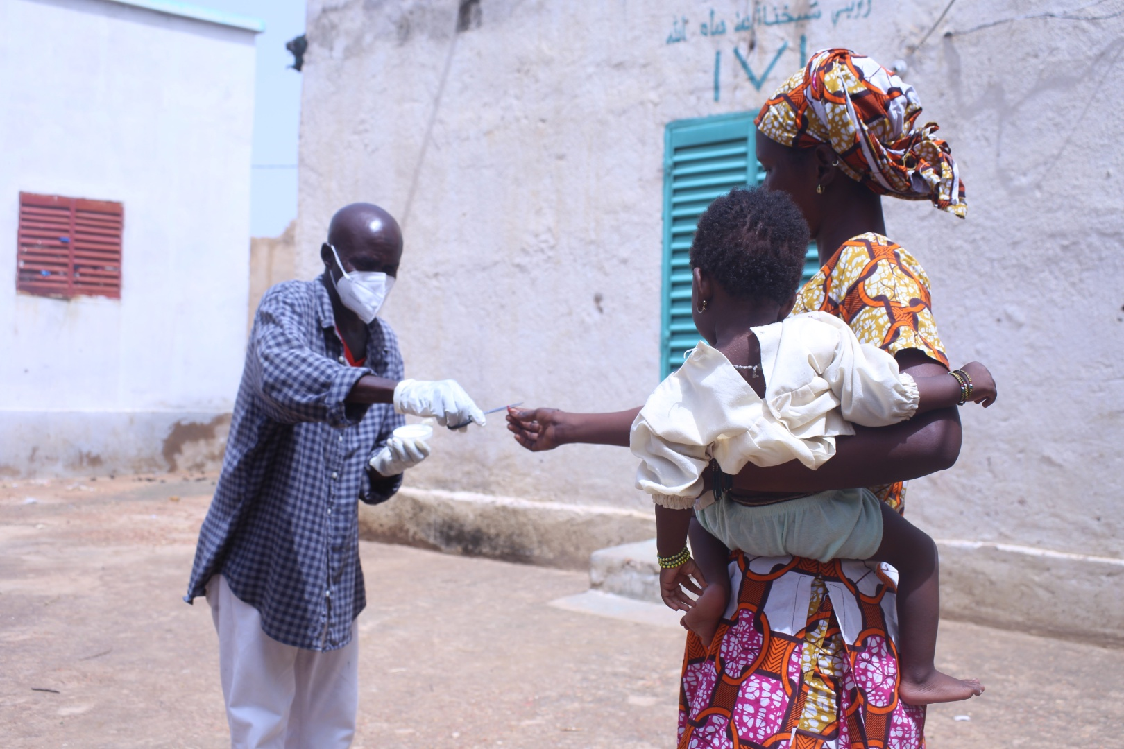 A health worker distances himself while preparing to deliver a dose of vitamin A to a young child being held by its mother