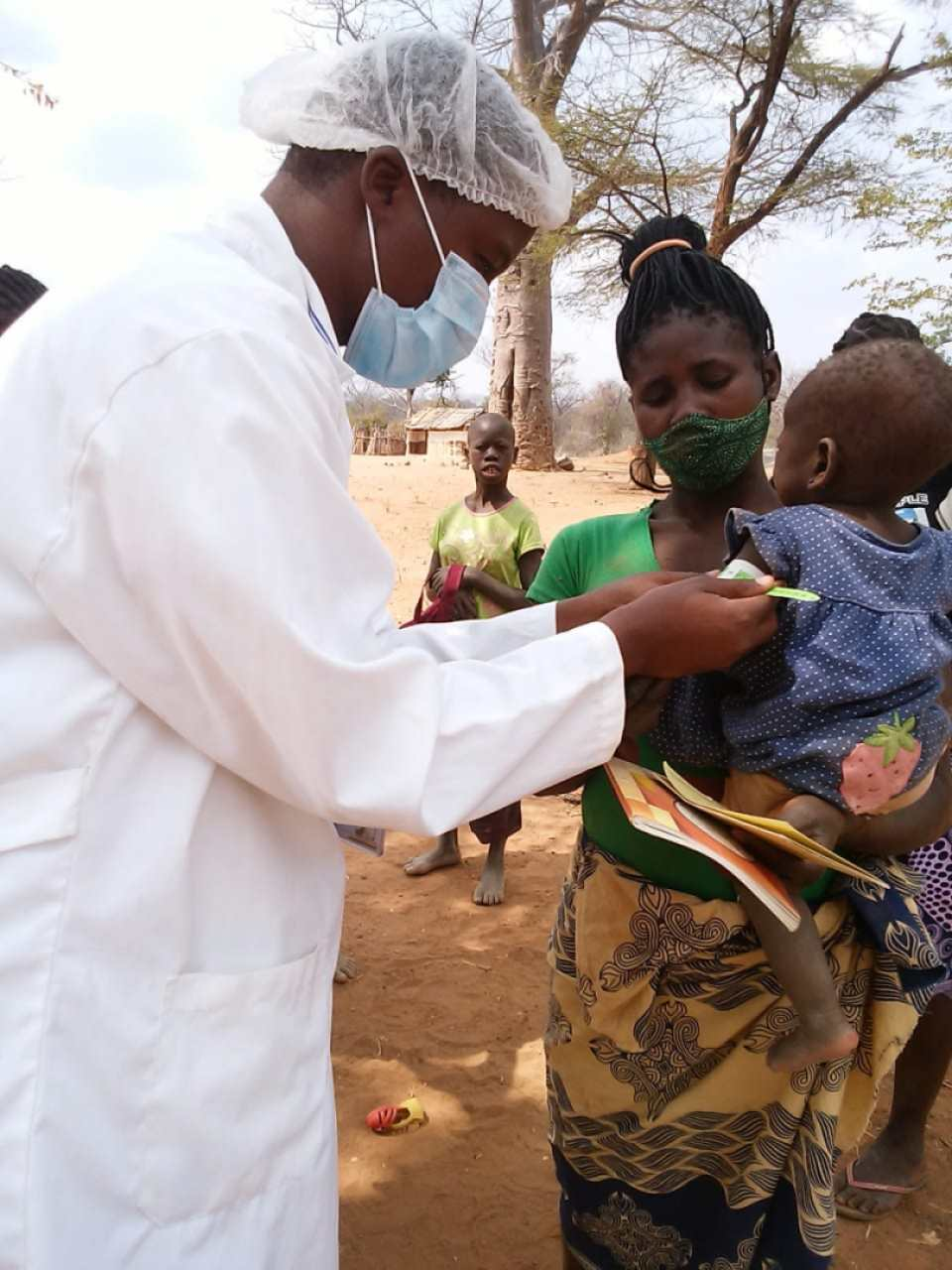 A health care worker screening a young child for malnutrition