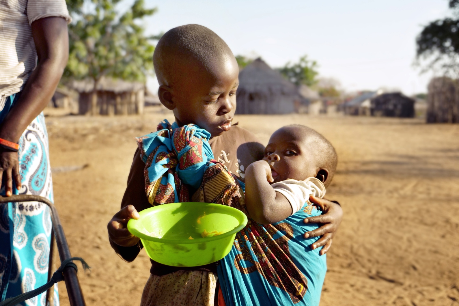 A boy holds a young child, wrapped in fabric