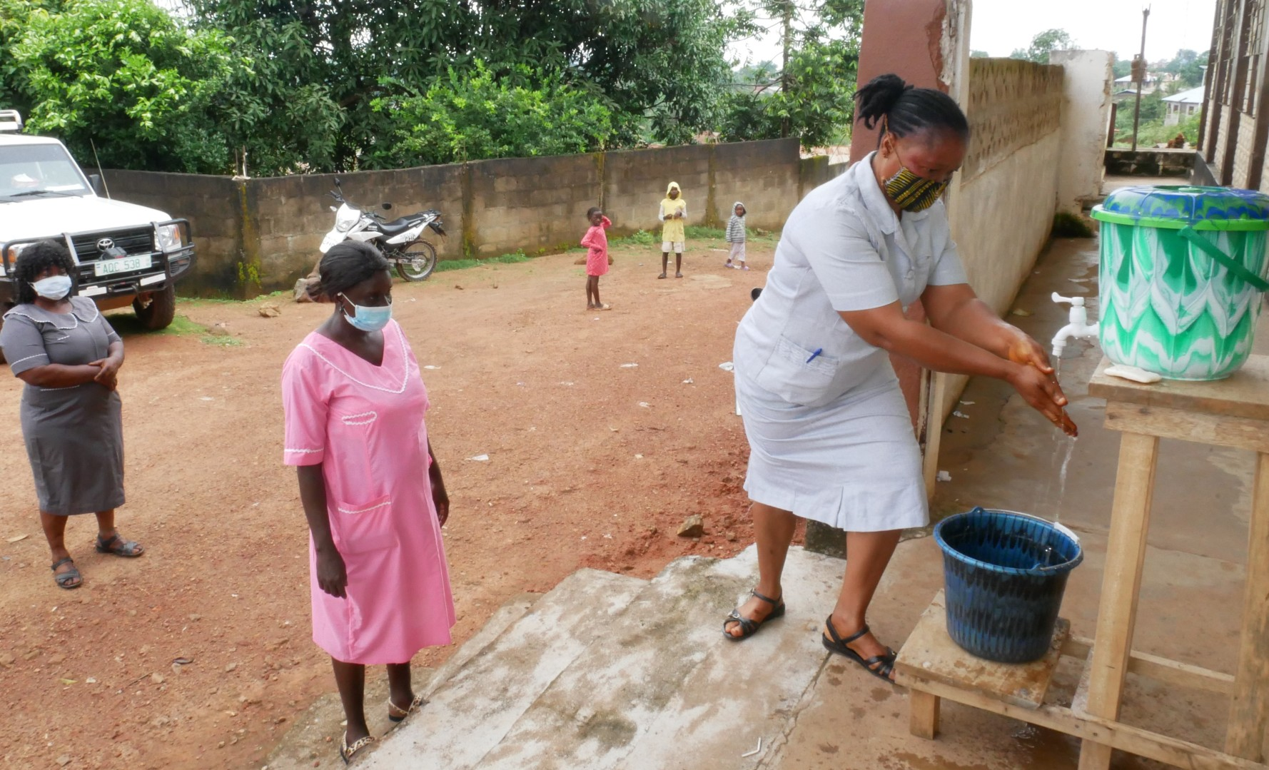 A health worker demonstrates how to use a handwashing station.