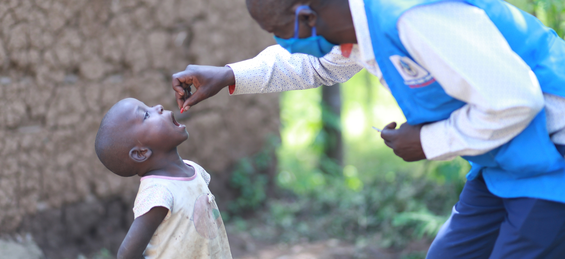 A health worker squeezes a dose of Vitamin A into a small child's mouth