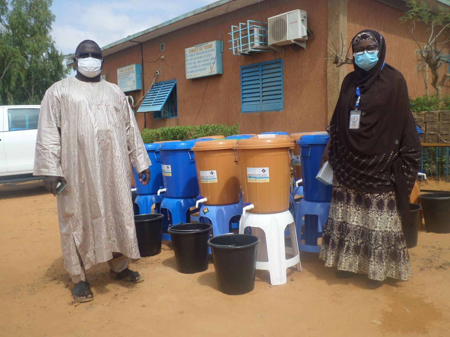 Health workers stand next to handwashing stations in Niger