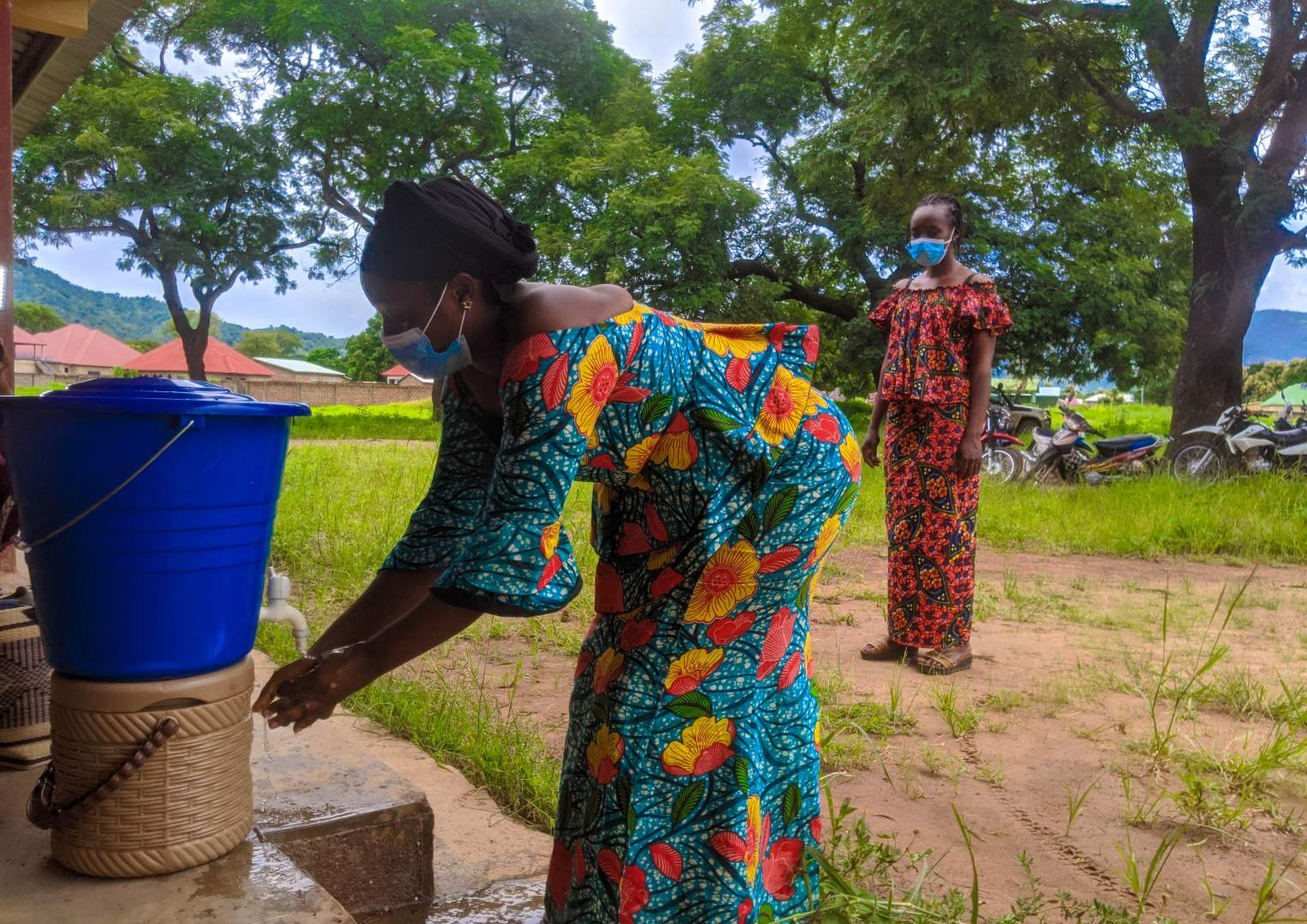 A woman washes her hands using a spout from a small bucket of water.