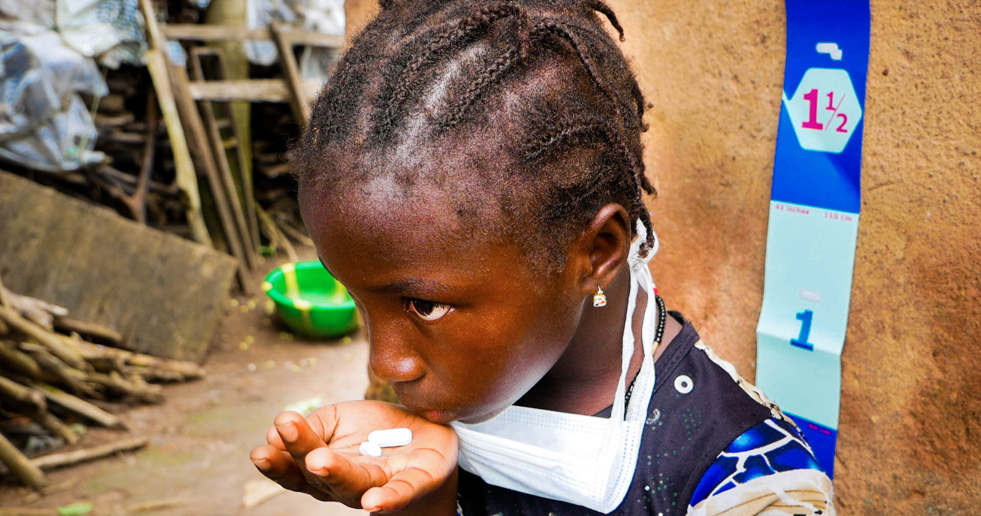 A young girl holds two pills, used to prevent and treat neglected tropical diseases.