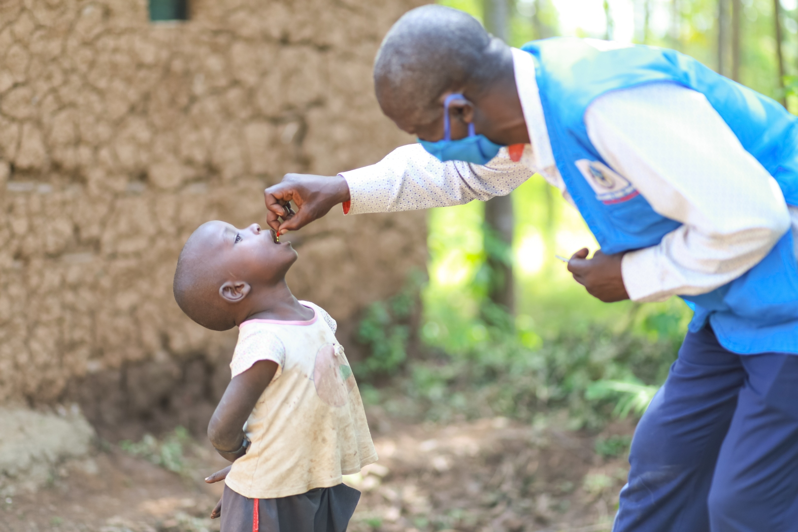 A health worker administers vitamin A drops to a child in Kenya