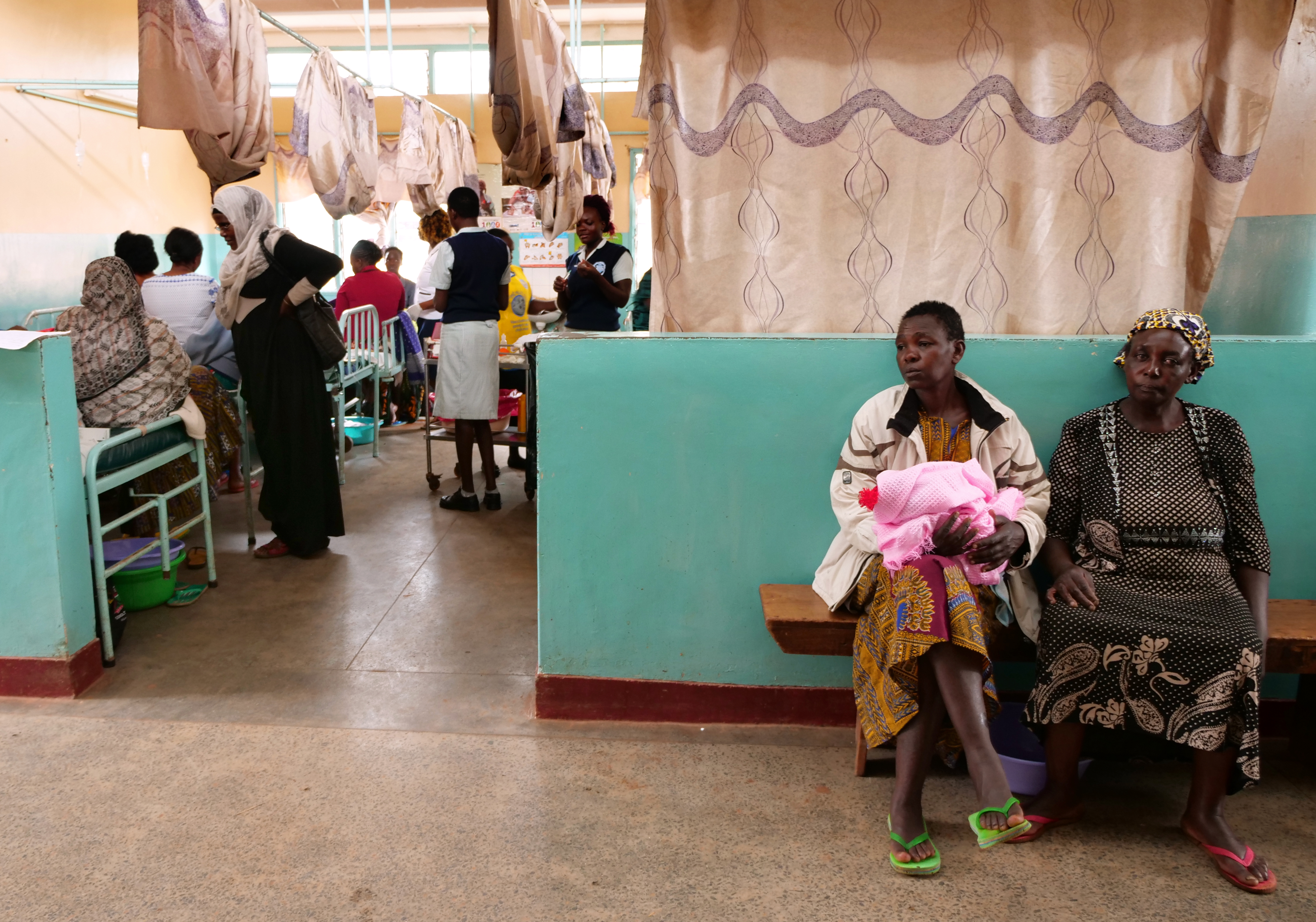 A mother sits with her newborn baby in the maternity care ward at Kitale County Referral Hospital.