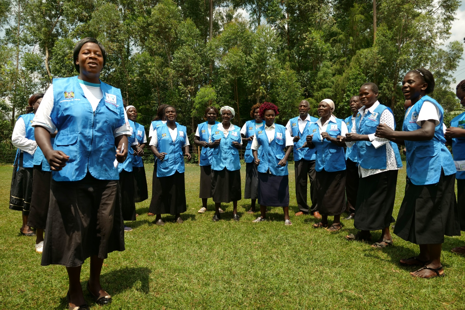 Community health volunteers stand and sing a song about the importance of maternal health care