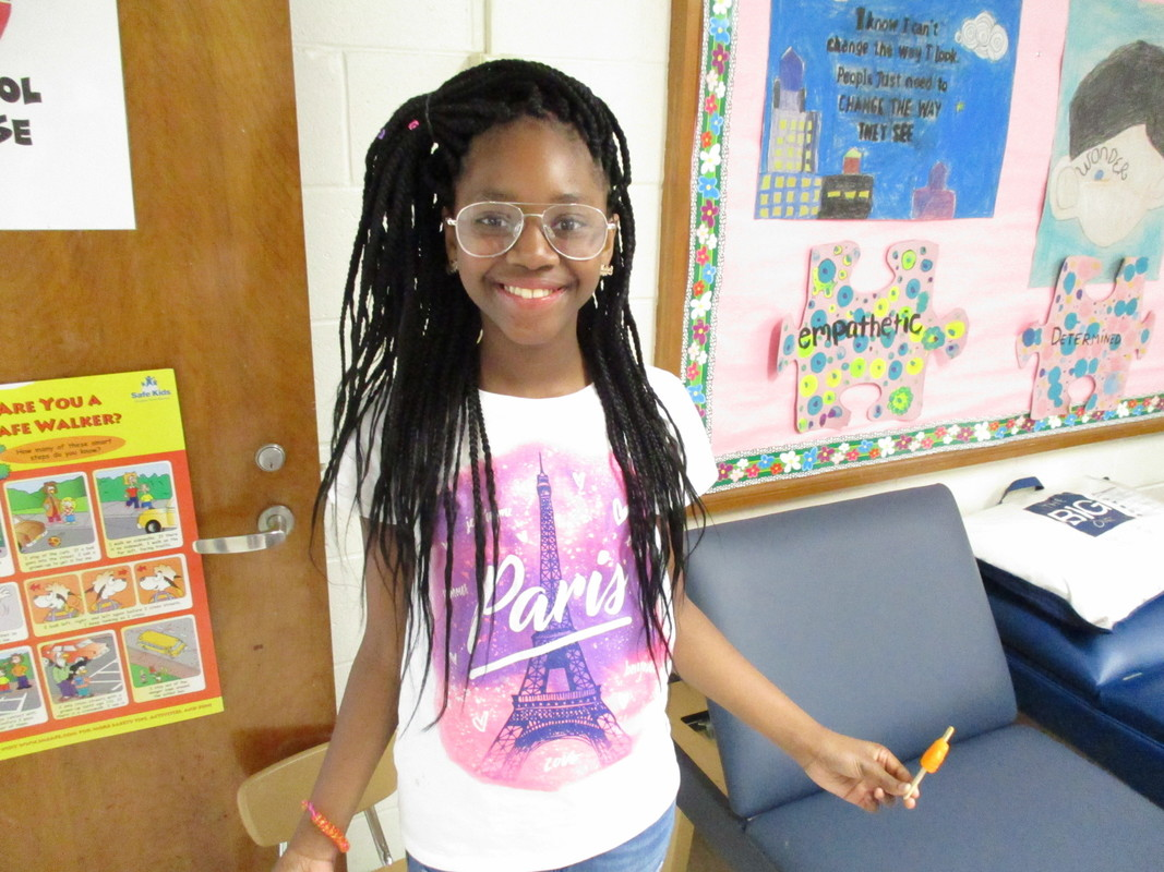 A young girl smiles while wearing her new eyeglasses