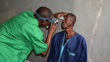 A health care worker examines the eye of a patient