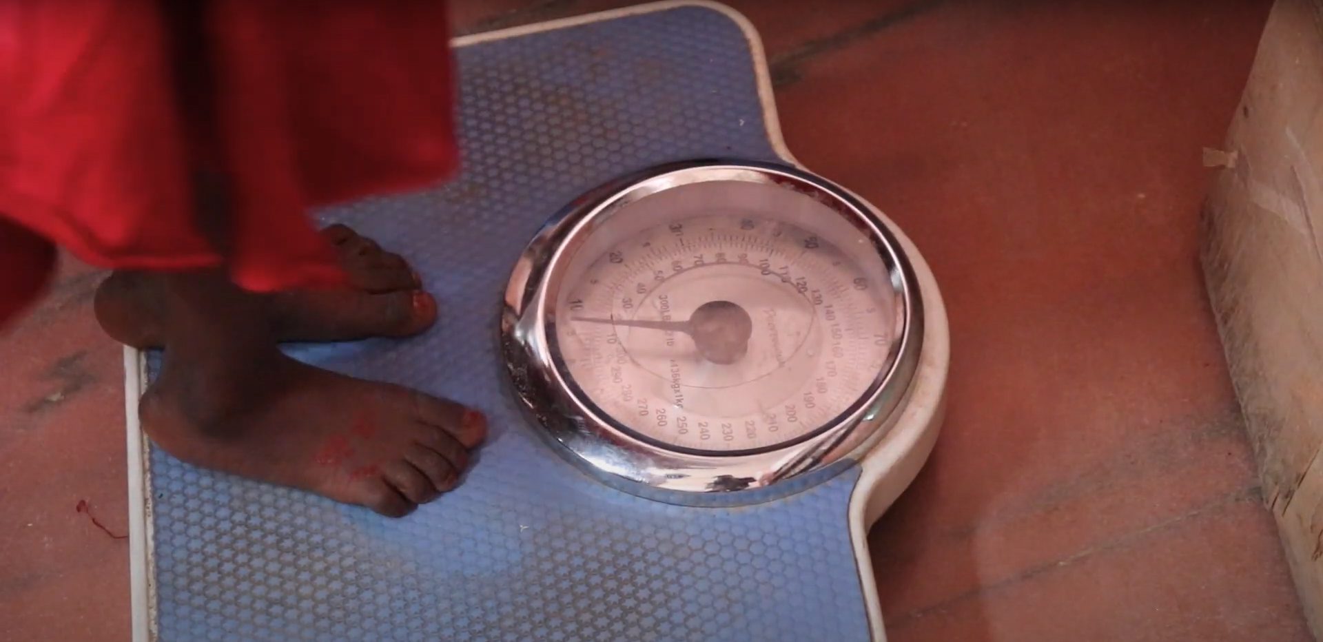 A child's feet standing on top of a scale