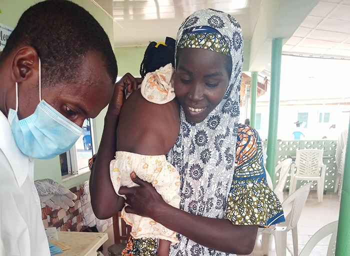 Health worker checking Adama's weight at the CMAM centre on her fourth follow up visit
