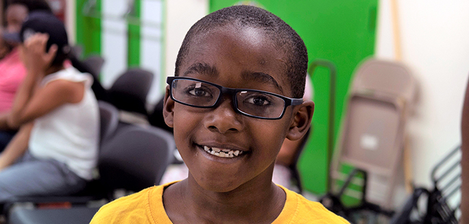 Eight-year-old Ezekiel wearing his new glasses
