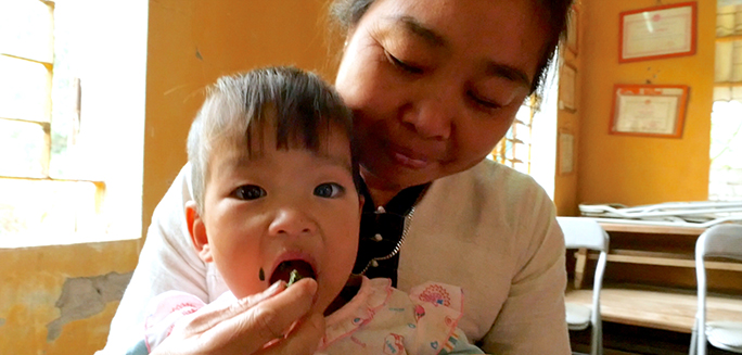 mother feeding her child in Vietnam